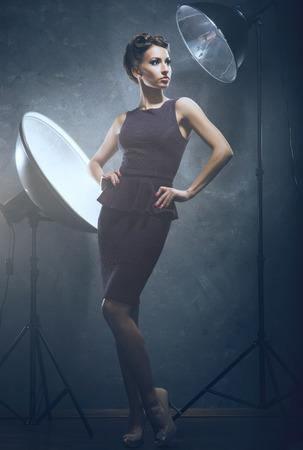 mujer joven y emocional en vestido de la manera sobre el fondo de glamour (estudio fotográfico detrás del escenario)