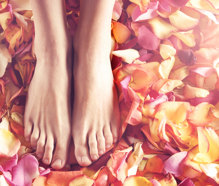 pedicure: Beautiful female legs over spa background. Stock Photo