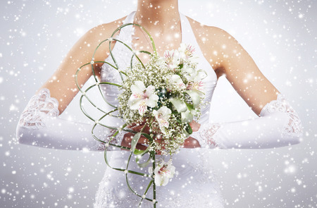 Beautiful wedding bouquet in brides hands. Winter background with a snowflakes.