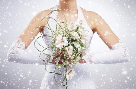 mujer con rosas: Ramo de la boda hermosa en manos de la novia. Fondo de invierno con copos de nieve.