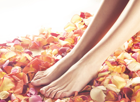 feet in water: Beautiful female legs over spa background. Stock Photo