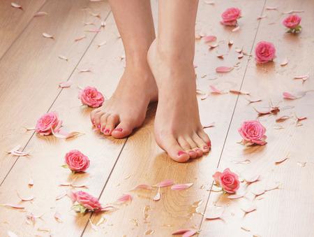 女性のセクシーな脚と多くの異なる花びらと花のスパ組成