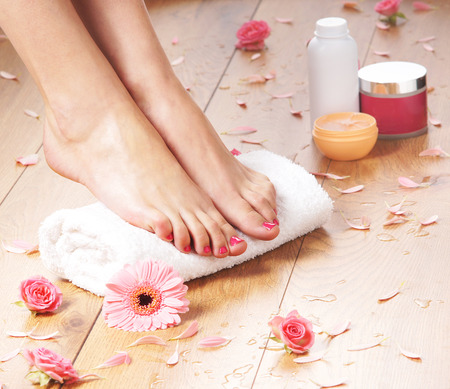 pedicure: Spa compositions of sexy female legs and plenty of different petals and flowers Stock Photo
