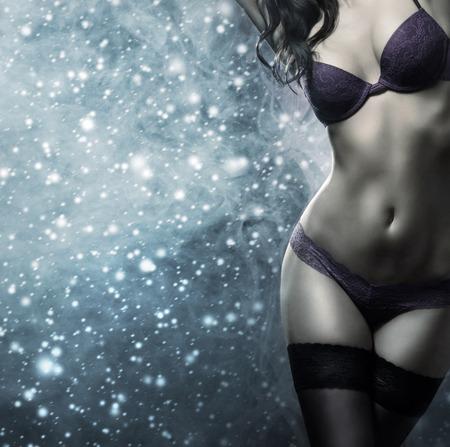 ropa interior femenina: Cuerpo de mujer joven y hermosa en ropa interior atractiva sobre el fondo cubierto de nieve de invierno Foto de archivo