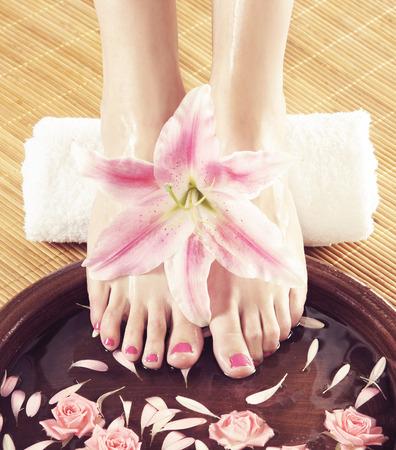 lirio blanco: Piernas hermosas, flores, pétalos y un tazón de cerámica. Fondo del balneario de verano. Foto de archivo