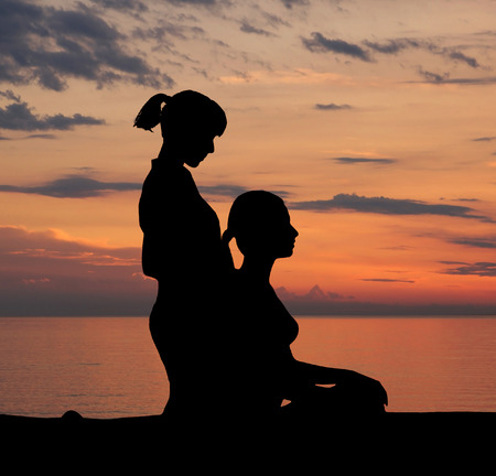 traditional healer: Trace of young woman getting traditional thai stretching massage by therapist isolated on the sunset background