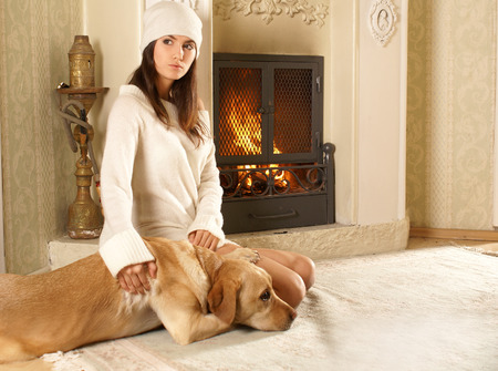 indore: Attractive woman with the dog near the fireplace