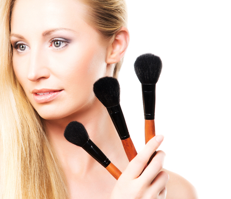 visage: Beauty portrait of young, attractive, fresh, healthy and natural woman with the makeup brush isolated on white Stock Photo