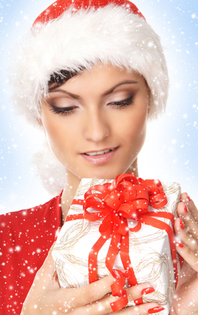 Portrait of young, sexy female Santa over Christmas background