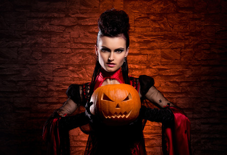 satanist: Halloween concept: young and sexy lady vampire in the dungeon