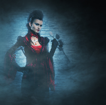 satanist: Beautiful, young and sexy female vampire over the smoky background. Halloween concept.