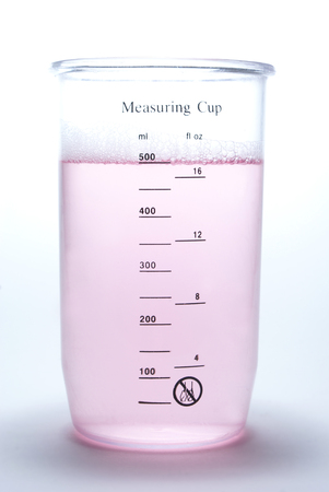red gram: Measuring cup with liquid on white  background Stock Photo