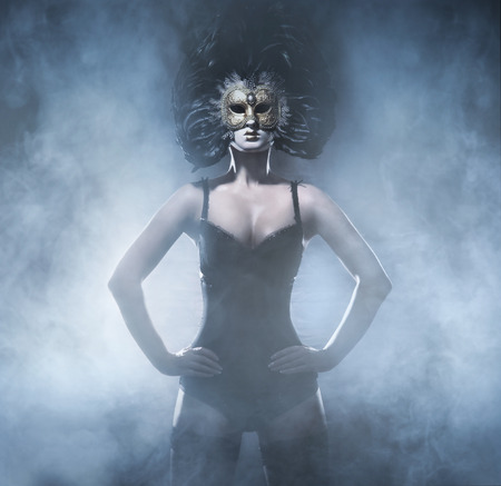 Sexy and bizarre woman in mask and lingerie over the smoky background Stock Photo