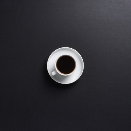 drinking coffee: Cup of coffee over the black background Stock Photo
