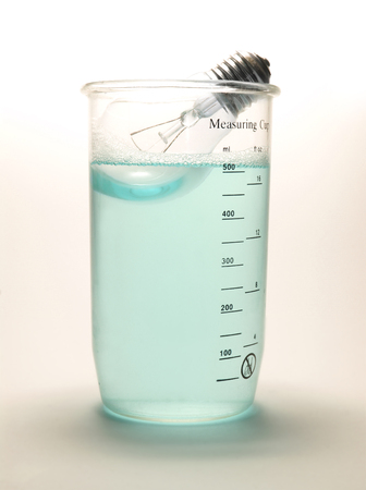 red gram: Lamp in blue liquid in measuring cup on white Stock Photo