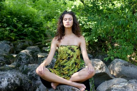 mujer meditando: La mujer sana joven meditando en el bosque