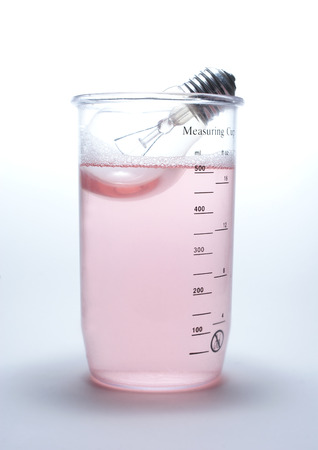 red gram: Lamp in rose liquid in measuring cup on white