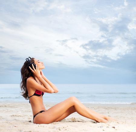 vientre femenino: Mujer hermosa en traje de baño relajante en una playa Foto de archivo