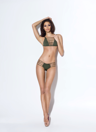 mujeres eroticas: Fashion photo of beautiful and young lady in swimsuits posing in studio Foto de archivo