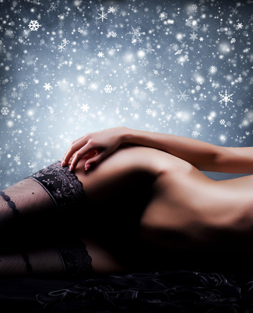 nude christmas: Naked body over snowy Christmas background
