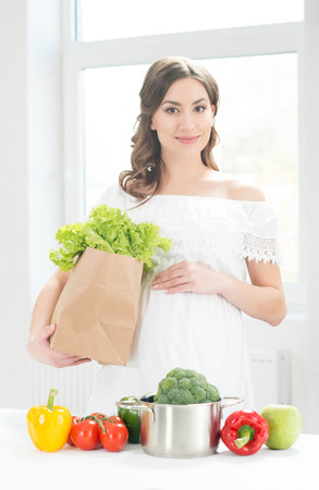 Beautiful pregnant woman with a shopping bag in the kitchen. Standard-Bild