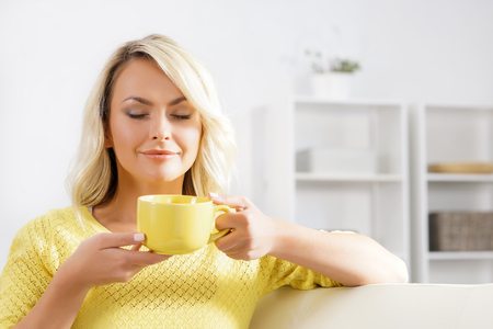 Beautiful woman enjoying the smell of coffee in the morning. Stock Photo