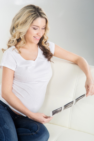birthing: Beautiful pregnant blond watching her foetus ultrasound scans. Stock Photo