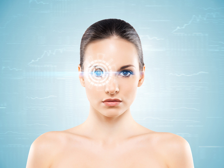 Young and attractive woman from future with the laser hologram on her eyes (collage about eye scanning technology) Stock Photo