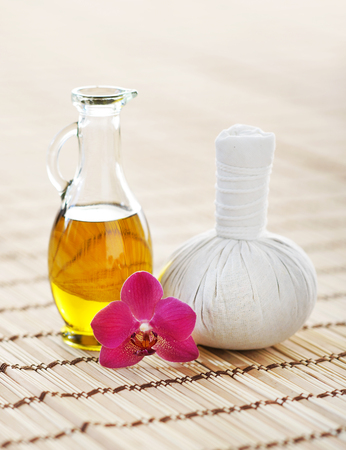 fragrant: Spa aromatherapy composition with fragrant oil, orchid and ball on bamboo mat over isolated background.