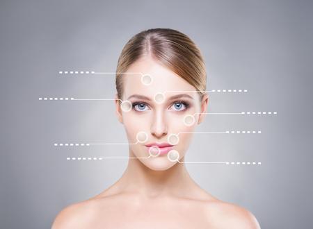 Attraktive Mädchen mit Pfeilen zeigt auf verschiedene Teile des Gesichts. Medizinisches Konzept. Standard-Bild