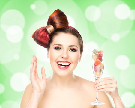 Beautiful smiling woman holding a wineglass with candies on bubbly background.