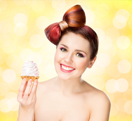 Beautiful woman with a bow haircut holding a cake on bubbly background. Stock Photo