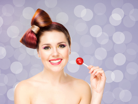 Beautiful smiling woman with a lollipop on bubble background. Stock Photo