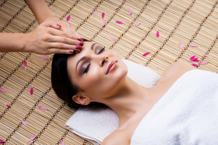 Beautiful, young and healthy woman on bamboo mat in spa salon having face massage. Spa, health and healing concept. Stock Photo