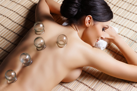 Beautiful, young and healthy woman on bamboo mat in spa salon is having vacuum cupping. Spa, health and healing concept.