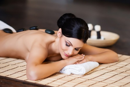 healer: Beautiful, young and healthy woman on bamboo mat in spa salon is having hot stone massage. Spa, health and healing concept.