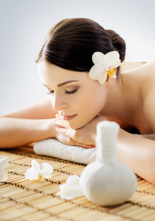 healer: Young and beautiful girl relaxing in Christmas spa salon. Massage therapy, healing medicine and health care concept.