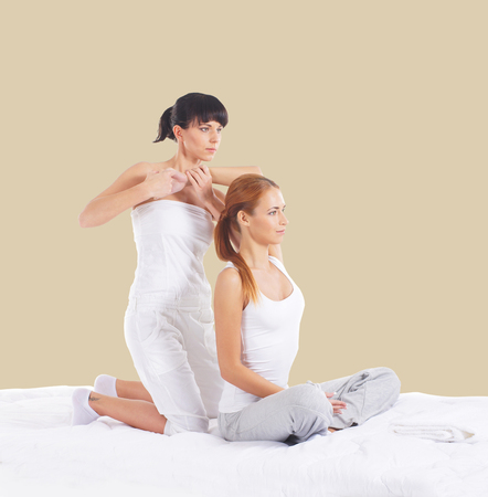 healer: Young woman getting traditional thai stretching massage by therapist over beige background