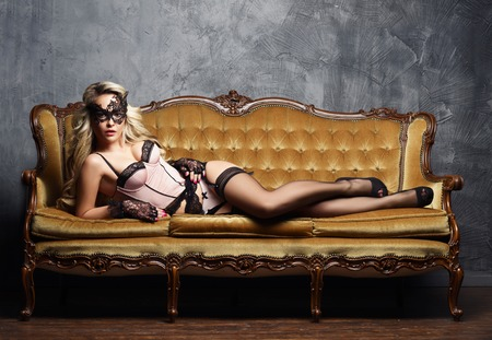 Sexy and beautiful woman in erotic lingerie and stockings posing on a sofa in vintage interior. Фото со стока