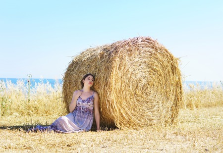 Young, emotional and happy woman in a meadow of rye. Beautiful girl in a white dress. Summer concept.