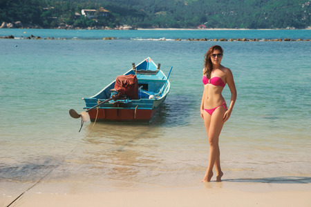 Hot, sexy woman wearing sunglasses and pink bikini posing on the seacoast over background with boat.
