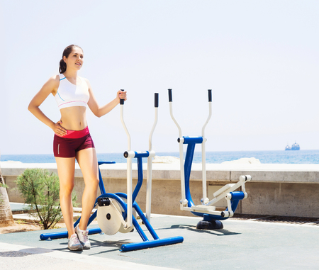cross legs: Fit and sporty woman training outside. Girl exercising on a sport machine in outdoor gym.