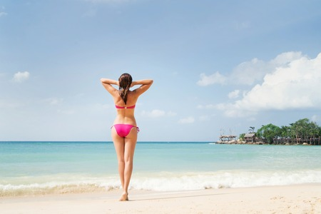Young, gorgeous lady with seductive legs in alluring pink swimwear relaxing on the beach.