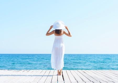 Vrouw in witte jurk op een houten pier op zomer. Zee en lucht achtergrond. Vakantie, reizen en vrijheid concept.