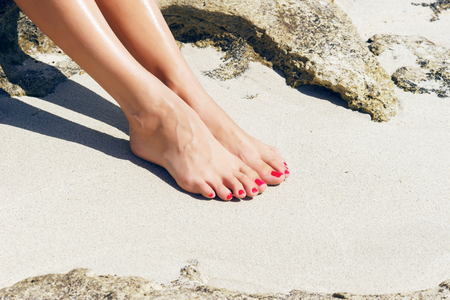 Pretty woman feet with red pedicure: relaxing on sand. Holiday, vacation, spa, summer: concept. Standard-Bild