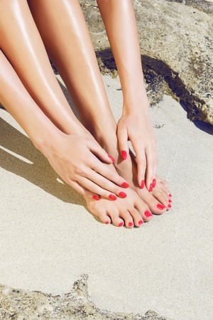 Pretty woman feet and hands with red pedicure and manicure: relaxing on sand. Holiday, vacation, spa, summer: concept. Standard-Bild