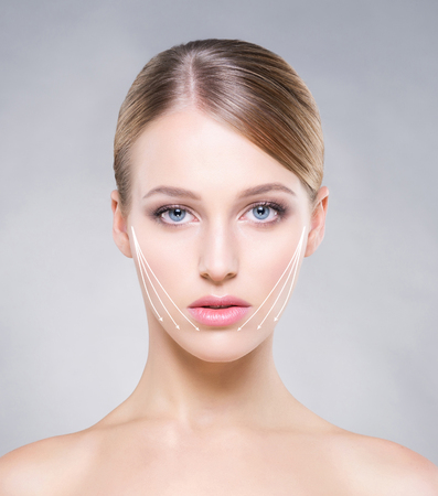 Portrait of attractive, healthy woman with smooth skin over grey background. Face lifting concept. Standard-Bild