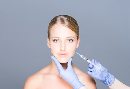 Doctor injecting botox in a beautiful face of a young woman. Plastic surgery concept.