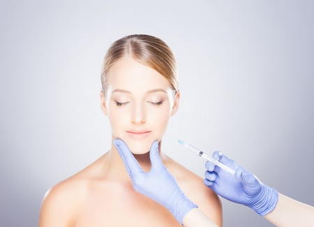 Doctor injecting in a beautiful face of a young woman. Plastic surgery concept. Stock Photo