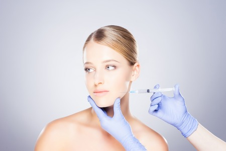 Doctor injecting in a beautiful face of a young woman. Plastic surgery concept. Standard-Bild